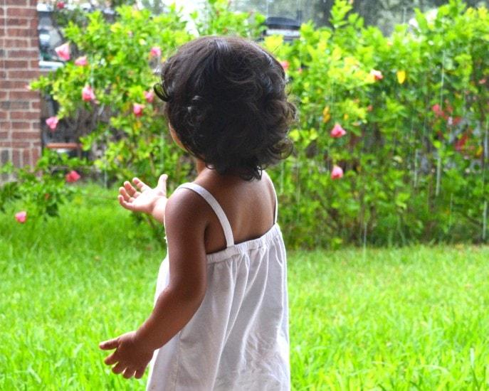 child catching raindrops